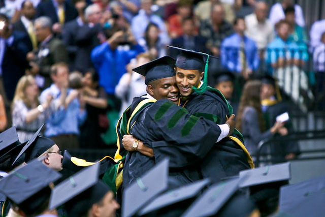 M11 Xavier Belcher hugs a classmate at graduation.